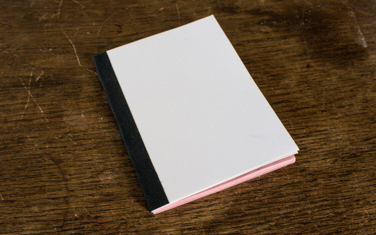 softcover notebook with white cover, pink paper on the inside and black tape on the spine